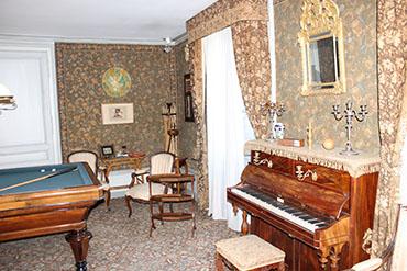 Ao lado, a sala de estar, com um piano...