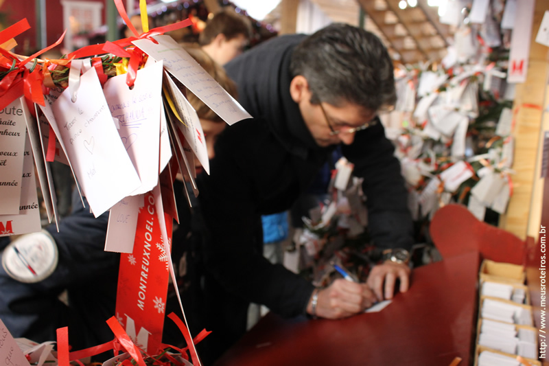 Homem com placa oferecendo abraço aos visitantes do mercado