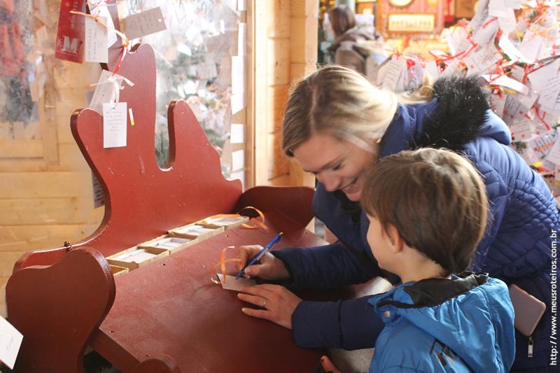 Mulher com crianças escrevendo bilhete para papai noel